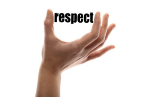 "Color horizontal shot of a of a hand squeezing the word ""respect""."